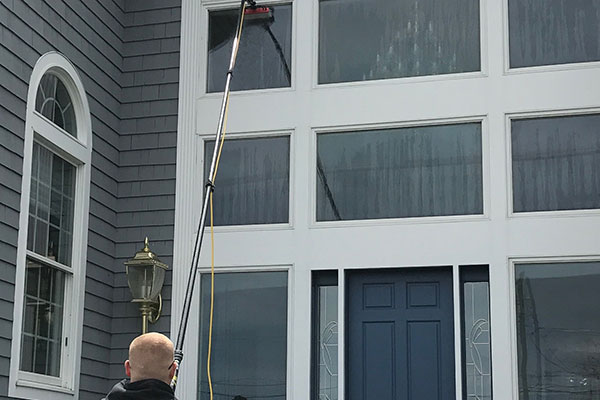 Joe cleaning a houses' window with pure water.