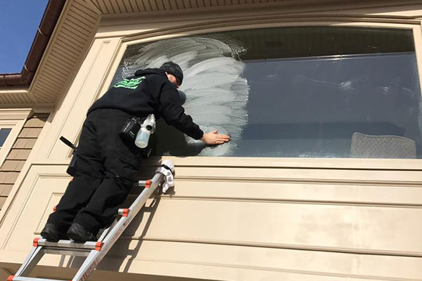 Joe cleaning a window exterior.